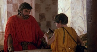 Curly-haired Greek king Agamemnon (Sean Connery) is prepared to adopt Kevin (Craig Warnock), to his gratitude.
