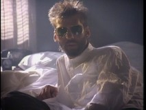 "With sunglasses and a wrinkled oversized shirt, Kenny Loggins looks very... dangerous in his ""Danger Zone"" music video."