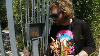 "T.J. Miller has trouble getting in to present Michael Bay with this Transformers fruit arrangement in ""T.J. Miller: Farm Hippie."""