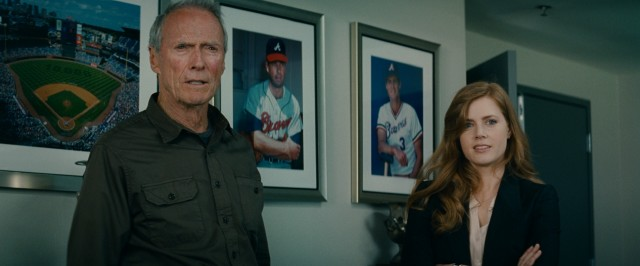 The father scowls, the daughter smiles. Together, Clint Eastwood and Amy Adams are... the baseball family!