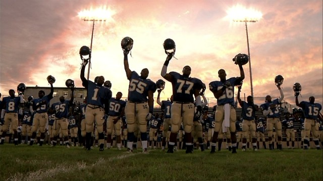 "The players of Manassas High School's football team hold their helmets high for the homecoming game, an image that has become the cover art for the Oscar-winning documentary ""Undefeated."""