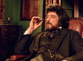 Samson Flusky (John Hallam) listens to conflicting accounts with a thin cigar in his hand.