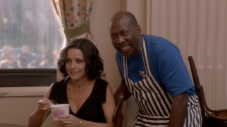 An unwell Selina (Julia Louis-Dreyfus) poses for an unflattering photograph with the frozen yogurt store owner (Brent Jennings) who dedicates a flavor to her.