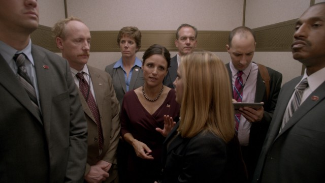 Flanked by secret service, Selina Meyer (Julia Louis-Dreyfus) continues to consult staffers (Matt Walsh, Anna Chlumsky, and Tony Hale) on an elevator ride to a public function.