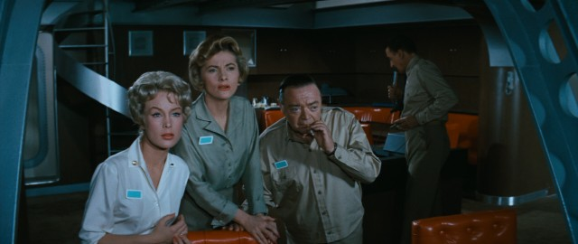 Lt. Connors (Barbara Eden), Dr. Hiller (Joan Fontaine), and Commodore Emery (Peter Lorre) get an up-close look at the underwater action occurring outside the Seaview's large windows.