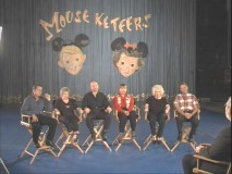 "Six of the original Mouseketeers gather in front of the show's curtain and remember ""The Leader of the Club."""