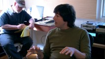 Composer Thomas Newman shares ideas, while the capped, bearded man in the corner jots them down on a legal pad.