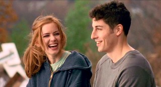 Katie and Anderson (Jason Biggs) share a laugh while sitting atop a hill of junk.