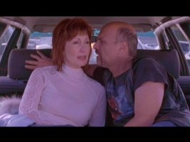 Lois (Joanna Gleeson) and Smitty (Joe Pantoliano) share an intimate conversation in the very back of an open car.