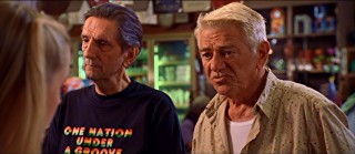 Skip (Harry Dean Stanton) and Boyd (Seymour Cassel) chat up a pair of young ladies while purchasing, among other things, a One Nation Under a Groove t-shirt.