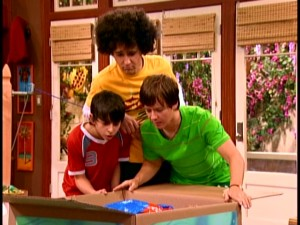 After a bit of work, Oliver (Mitchel Musso), Rico (Moises Arias), and Jackson (Jason Earles) look at the intriguing box opened and beeping. A joke stemming from steam, Musso's puffy afro actually improves upon his regular shaggy look.