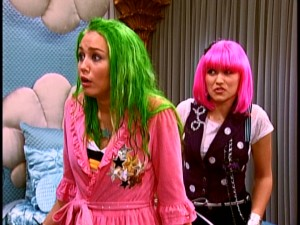 Miley (Miley Cyrus) finds her hair has turned green, thanks to a miscalculation by best friend Lilly (Emily Osment).