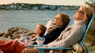 Three generations of Haines women (India Ennenga, Meg Ryan, and Candice Bergen) soak in the sun by a scenic New England coast and lighthouse.