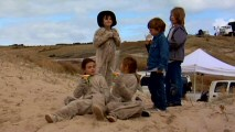 "Children, including three dressed in Max's wolf suit, enjoy refreshment and conversation on the sandy Australian set in ""The Kids Take Over the Picture."""