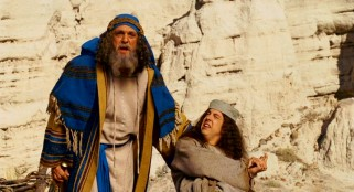 Abraham (Hank Azaria) pauses from sacrificing son Isaac (Christopher Mintz-Plasse) to hear his visitors.