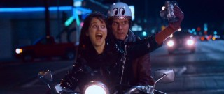 The free-spirited Allison (Zooey Deschanel) takes a photograph of herself and Carl while they share a nighttime scooter ride.