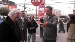"David Fincher directs Brian Cox and others from the sidewalk of an outdoor scene in ""Zodiac Deciphered."""