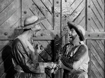 These two men -- let's call them Pancho (Frank Yaconelli) and Pepe (Nick Moro) -- are heartily amused by the sight of Zorro's Z on this set of doors.