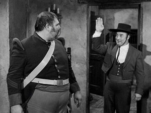 Bernardo (Gene Sheldon) waves to Sergeant Garcia (Henry Calvin) in an impromptu attempt to hide that he hears more than he lets on.
