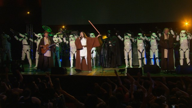 "The Force is with Weird Al on ""The Saga Begins"", a number that finds him joined by stormtroopers, Jedi knights, and Darth Vader himself, while the audience waves their arms in rhythm."