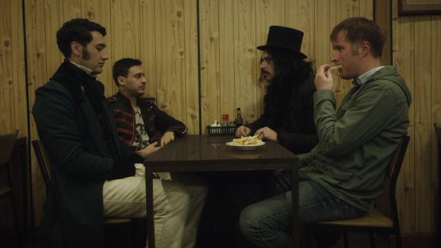 "Three vampires (Taika Waititi, Cori Gonzalez-Macuer, and Jemaine Clement) join their new human friend Stu (Stu Rutherford), as he grabs a bite to eat in ""What We Do in the Shadows."""