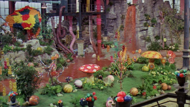 Wonka's Chocolate Room of river, waterfall, whipped cream mushrooms, and candy trees is introduced in this glorious pan shot.