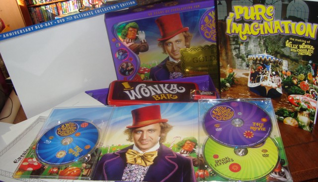 A look at the contents of the Willy Wonka and the Chocolate Factory 40th Anniversary Blu-ray + DVD Ultimate Collector's Edition: three discs, a big box, a book, an envelope of document reproductions, a Wonka Bar tin, a scented eraser, a sweepstakes golden ticket, and scratch-n-sniff pencils.