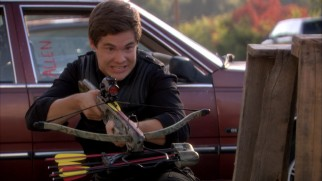 Adam (Adam DeVine) tries to figure out a crossbow as part of the guys' manly weekend hunting trip.