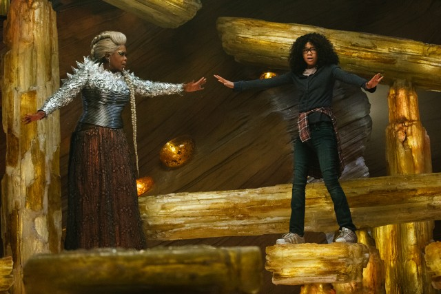 A normal-sized Mrs. Which (Oprah Winfrey) stands in support next to Meg (Storm Reid) as they consult the cave sage Happy Medium.